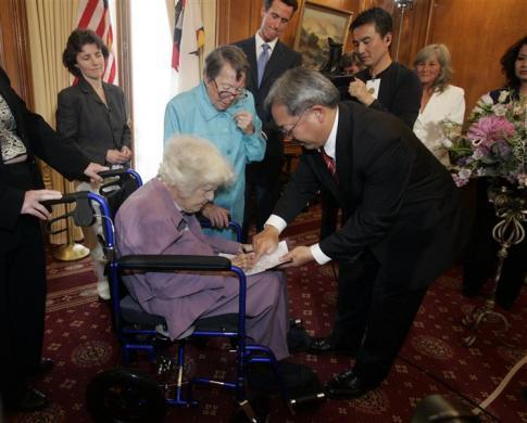 Octogenarian Phyllis Lyon (standing, 2nd L) watches as her partner Del Martin (bottom) signs their gay-marriage certificate in front of San Francisco county clerk Edwin Lee during the first legal same-sex marriage ceremony at San Francisco City Hall in San Francisco, California June 16, 2008. California performed its first legally recognized same-sex weddings and opened its doors to gay and lesbian couples from around the country, a move likely to challenge other states that define marriage as between a man and a woman. The ceremony was presided over by Mayor Gavin Newsom (back, 3rd L).