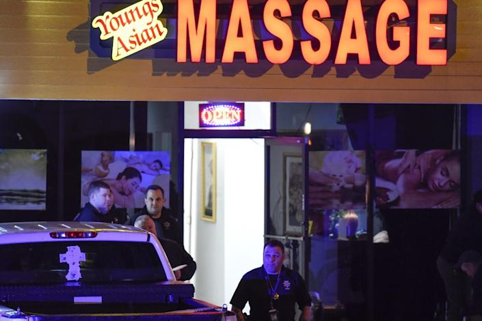 Police outside an Asian spa in a strip mall at night