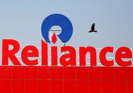 FILE PHOTO: A bird flies past a Reliance Industries logo installed on its mart in Ahmedabad