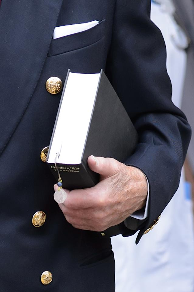 "The Duke of Edinburgh carries a book entitled ""Crucible of War"" by Fred Anderson as he leaves the London Clinic in central London, 11 days after he was admitted for exploratory abdominal surgery."