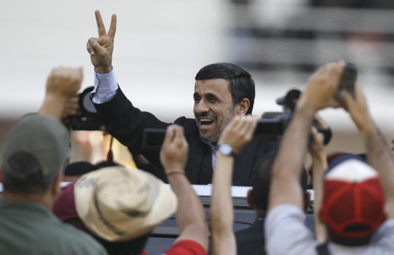 Iran's President Mahmoud Ahmadinejad makes a victory sign after attending the funeral ceremony for Venezuela's late President Hugo Chavez at the military academy in Caracas, Venezuela, Friday, March 8, 2013. Chavez died on March 5 after a nearly two-year bout with cancer.  He was 58.  (AP Photo/Fernando Llano)