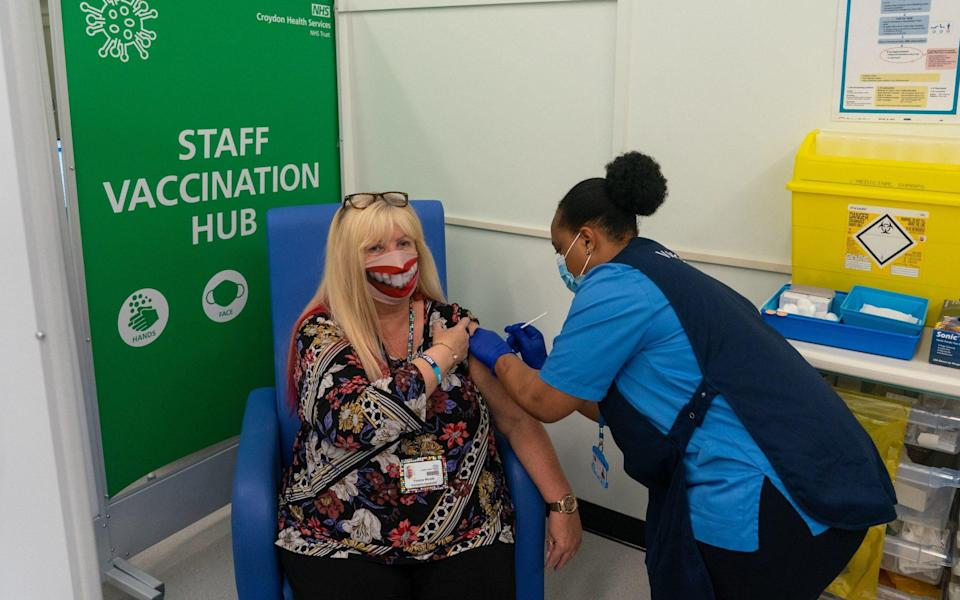 ...while Yvonne Woods wore a happy face mask to receive her booster - PA