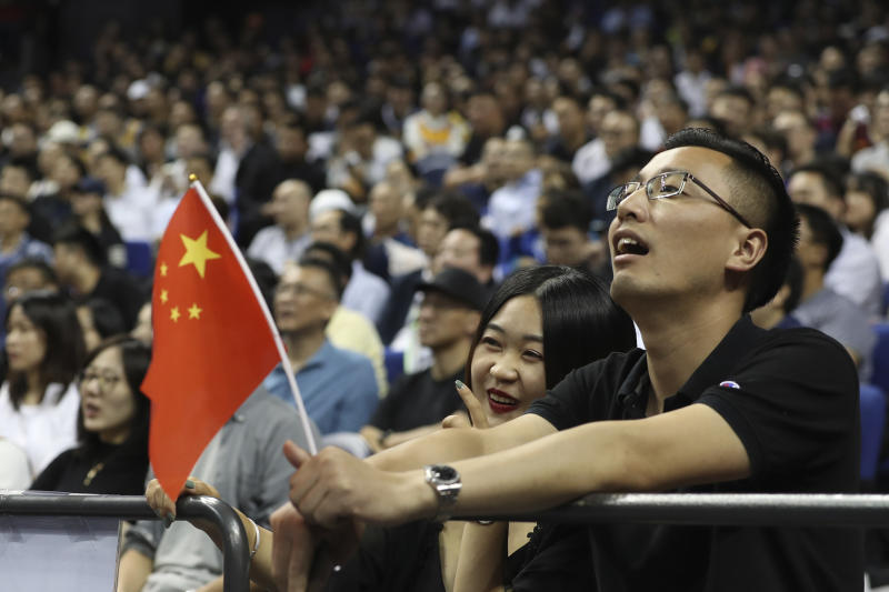 Chinese fans with a Chinese flag watch a preseason NBA basketball game between the Brooklyn Nets and Los Angeles Lakers at the Mercedes Benz Arena in Shanghai, China, Thursday, Oct. 10, 2019. (AP Photo)