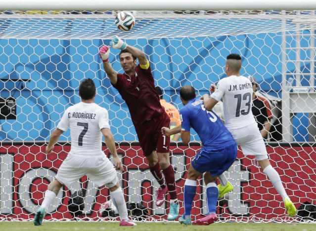 Italy's goalkeeper Gianluigi Buffon makes a save in front of Uruguay's Cristian Rodriguez (7) and Uruguay's Jose Maria Gimenez as Italy's Giorgio Chiellini defends during the group D World Cup soccer match between Italy and Uruguay at the Arena das Dunas in Natal, Brazil, Tuesday, June 24, 2014. (AP Photo/Petr David Josek)