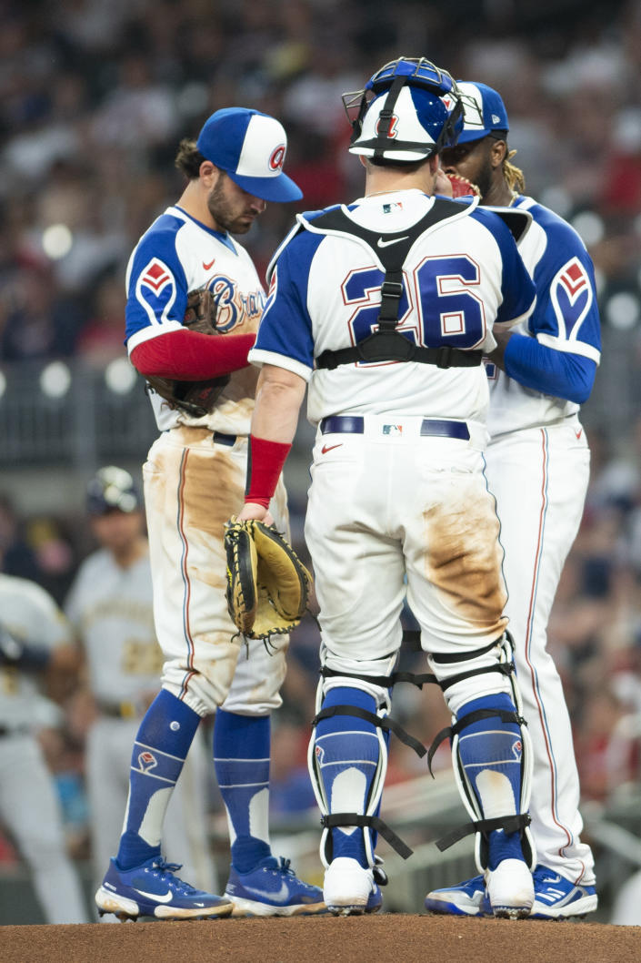 Atlanta Braves shortstop Dansby Swanson, left, and Atlanta Braves catcher Stephen Vogt (26) visit the mound to talk with starting pitcher Touki Toussaint, right, during the top of the third inning of a baseball against the Milwaukee Brewers, Friday, July 30, 2021, in Atlanta. (AP Photo/Hakim Wright Sr.)
