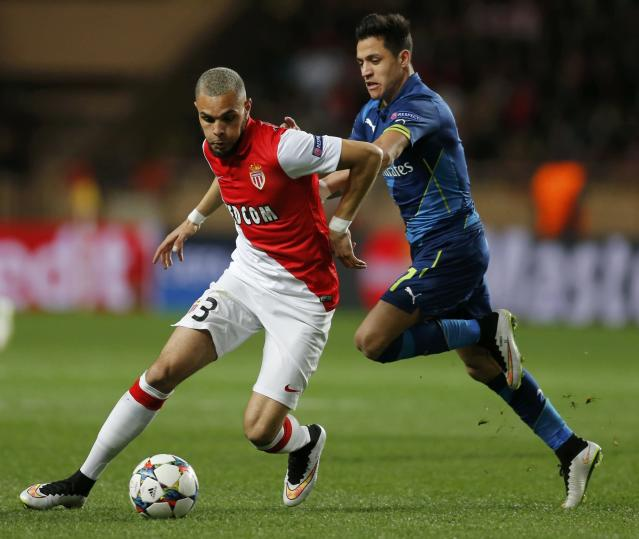 Monaco's Layvin Kurzawa (L) challenges Arsenal's Alexis Sanchez during their Champions League round of 16 second leg soccer match at the Louis II Stadium in Monaco, March 17, 2015. REUTERS/Jean-Paul Pelissier (MONACO - Tags: SPORT SOCCER)