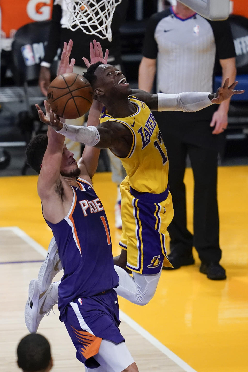 Los Angeles Lakers guard Dennis Schroder (17) shoots against Phoenix Suns guard Devin Booker (1) during the second quarter of Game 6 of an NBA basketball first-round playoff series Thursday, Jun 3, 2021, in Los Angeles. (AP Photo/Ashley Landis)