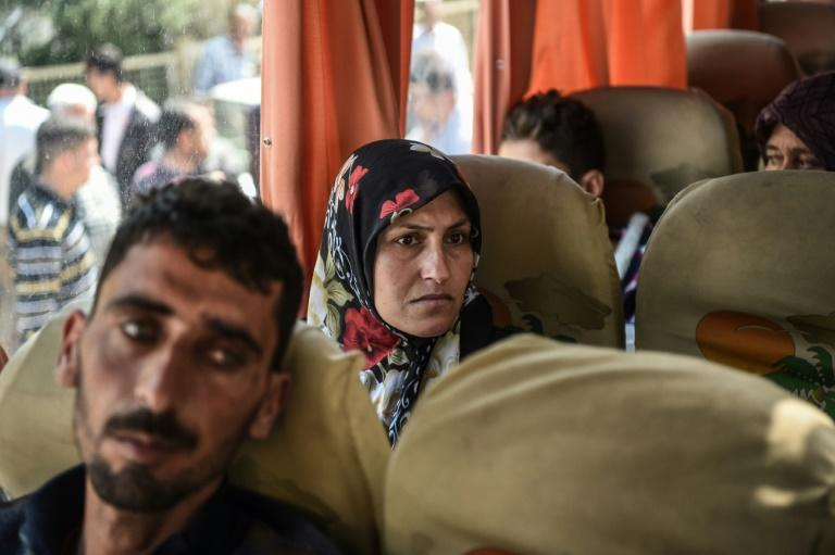 Syrian victims of a suspected chemical attack are carried in a bus back to the Syrian border after treatment in Turkey on April 7, 2017