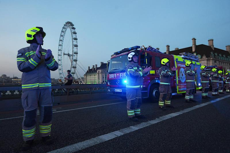 Fire fighters applaud on Westminster Bridge in London to salute local heroes (PA)