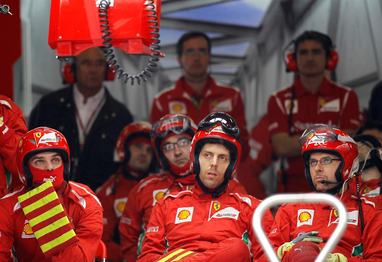Ferrari crew members follow the race from their garage during the Formula One Chinese Grand Prix at the Shanghai International Circuit on April 15, 2012.     AFP PHOTO / POOL / Aly Song (Photo credit should read ALY SONG/AFP/Getty Images)