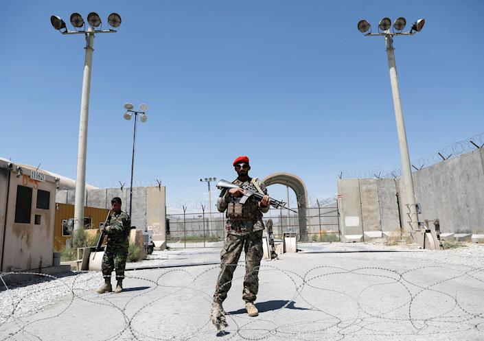 Image: Afghan soldiers stand guard at the gate of Bagram U.S. air base, on the day the last of American troops vacated it, Parwan province, Afghanistan (Mohammad Ismail / Reuters)