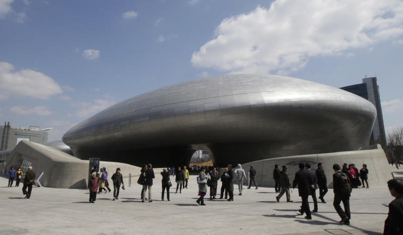 Visitors are dwarfed by Dongdaemun Design Plaza in Seoul, South Korea, Friday, March 21, 2014. The $450 million building funded by Seoul citizen's tax money finally opened to public on Friday after years of debates about transforming a historic area with an ultra-modern architecture.(AP Photo/Ahn Young-joon)