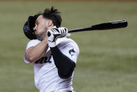 Miami Marlins' Adam Duvall loses his helmet as he swings at a pitch during the sixth inning of a baseball game against the Philadelphia Phillies, Monday, May 24, 2021, in Miami. (AP Photo/Wilfredo Lee)