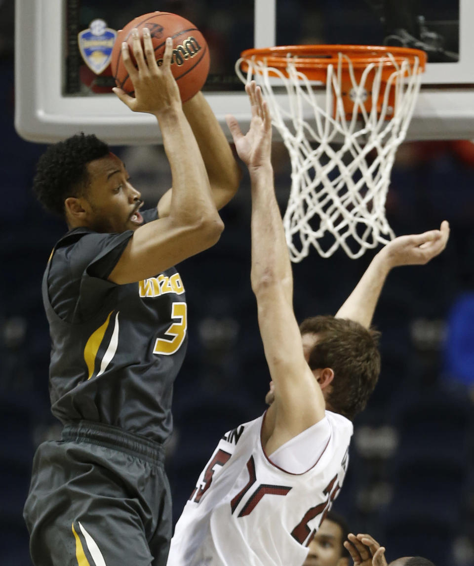 Missouri forward Johnathan Williams III (3) shoots as South Carolina forward Mindaugas Kacinas (25) defends during the second half of an NCAA college basketball game in the first round of the Southeastern Conference tournament, Wednesday, March 11, 2015, in Nashville, Tenn. (AP Photo/Steve Helber)