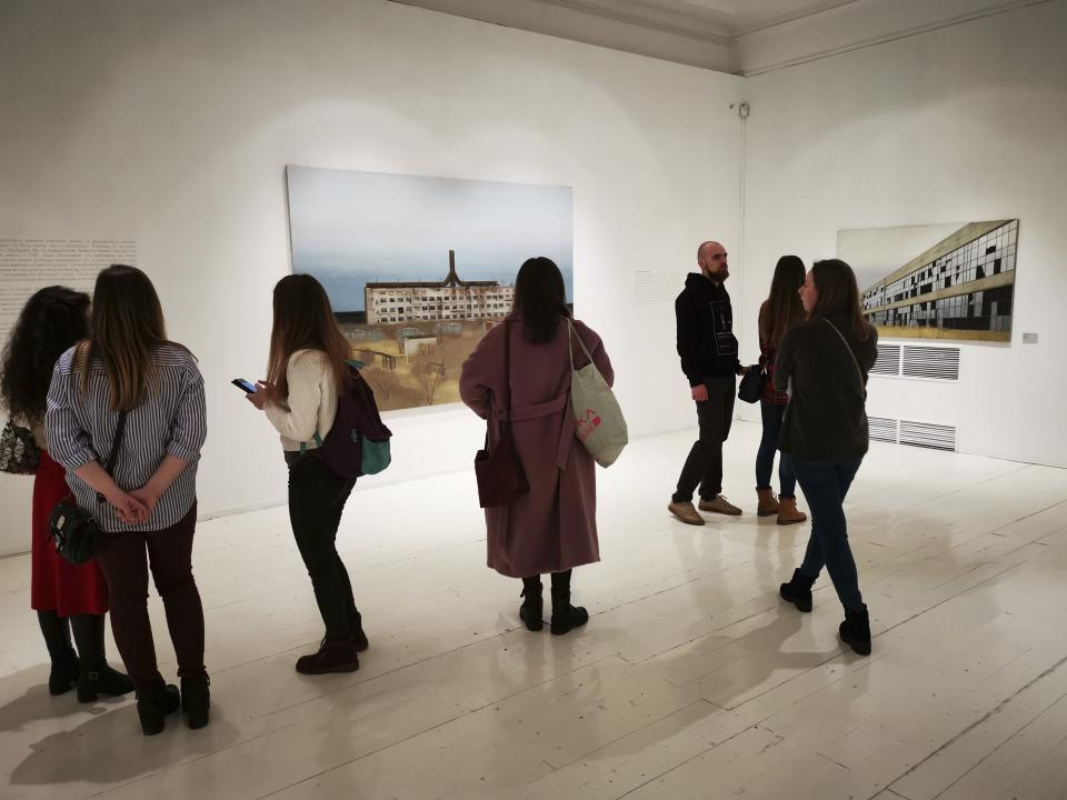 In this photo taken on Sunday, Feb. 17, 2019, visitors attend an exhibition by Russian artist Pavel Otdelnov in Moscow, Russia . Pavel Otdelnov, a Russian artist who grew up in Dzerzhinsk, the center of the nation's chemical industries 355 kilometers (220 miles) east of Moscow, focused on the city, one of the most polluted in Russia, in his new 'Promzona' art show. (AP Photo/Ivan Kochkarev)