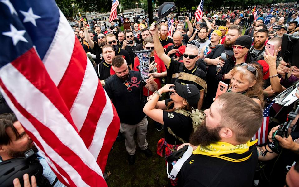 Members of the Proud Boys and other right-wing demonstrators plant a flag in Tom McCall Waterfront Park during a rally in Portland - Noah Berger