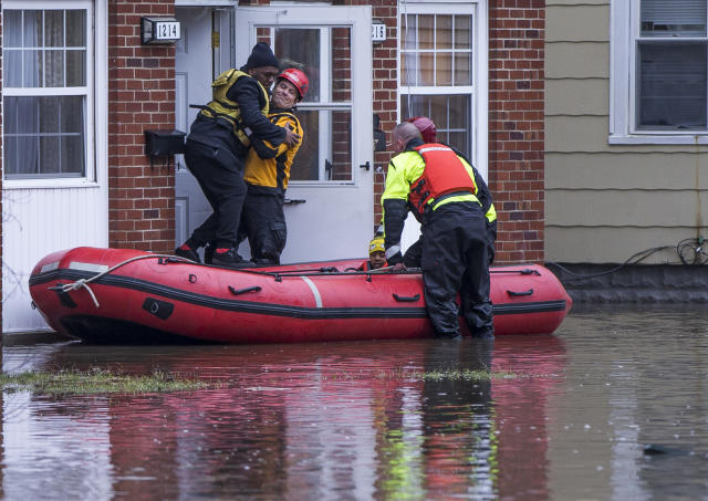 <p>A firefighter lifts 19-year-old Malik Williams and places him in a raft as they rescue him from rising flood waters at his home on Emerson Avenue Wednesday, Feb. 21, 2018, in South Bend, Ind. (Photo: Robert Franklin/South Bend Tribune via AP) </p>