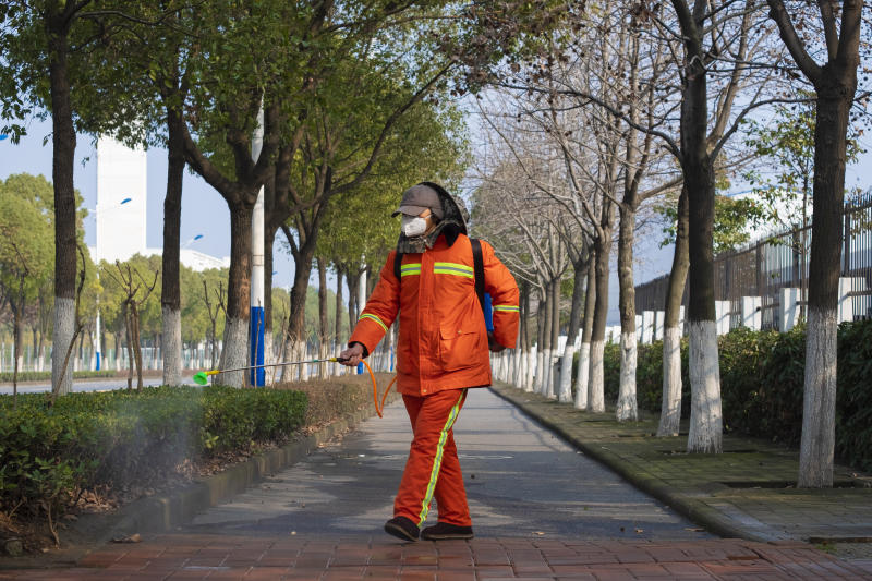 FILE - In this Jan. 28, 2020 file photo, a worker wearing a face mask sprays disinfectant along a path in Wuhan in central China's Hubei Province. Arek and Jenina Rataj were starting a new life in the Chinese industrial center of Wuhan when a viral outbreak spread across the city of 11 million. While they were relatively safe sheltering at home, Arek felt compelled to go out and document the outbreak of the new type of coronavirus. Among his subjects: the construction of a new hospital built in a handful of days; biosecurity check points; and empty streets.(AP Photo/Arek Rataj, File)