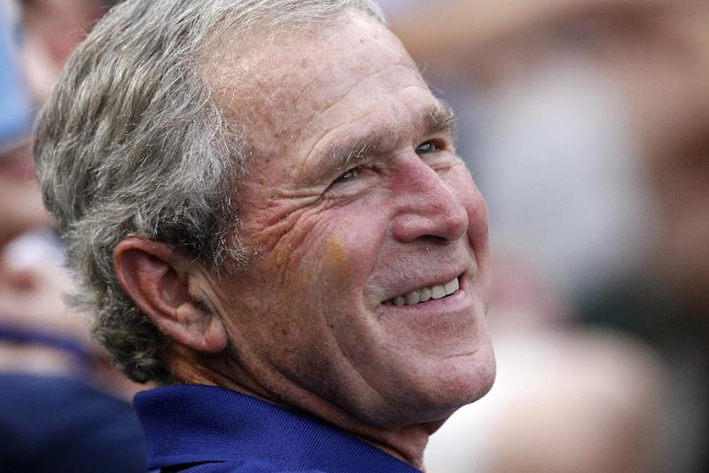 FILE - In this June 16, 2012 file photo, former President George W. Bush smiles as he takes in a baseball game in Arlington, Texas. The Rangers won 8-3. Sarah Palin and George W. Bush won't be in Tampa. Hillary Rodham Clinton and Al Gore aren't making the trip to Charlotte. And scores of other Republican and Democratic stars are taking a pass as their parties gather at every-four-years national conventions. The reasons are varied _ and political.  (AP Photo/LM Otero, File)