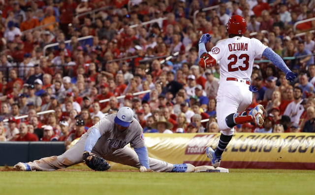 St. Louis Cardinals' Marcell Ozuna (23) is safe at first for a single as Chicago Cubs first baseman Anthony Rizzo misses the throw during the sixth inning of a baseball game, Sunday, June 17, 2018, in St. Louis. (AP Photo/Jeff Roberson)