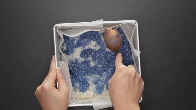 Compressing rice into baking tin with a spoon