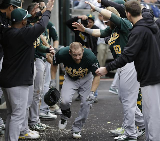 Oakland Athletics' Brandon Moss is cheered by teammates after his solo home run during the fifth inning of Game 3 of an American League baseball division series against the Detroit Tigers in Detroit, Monday, Oct. 7, 2013. (AP Photo/Paul Sancya)