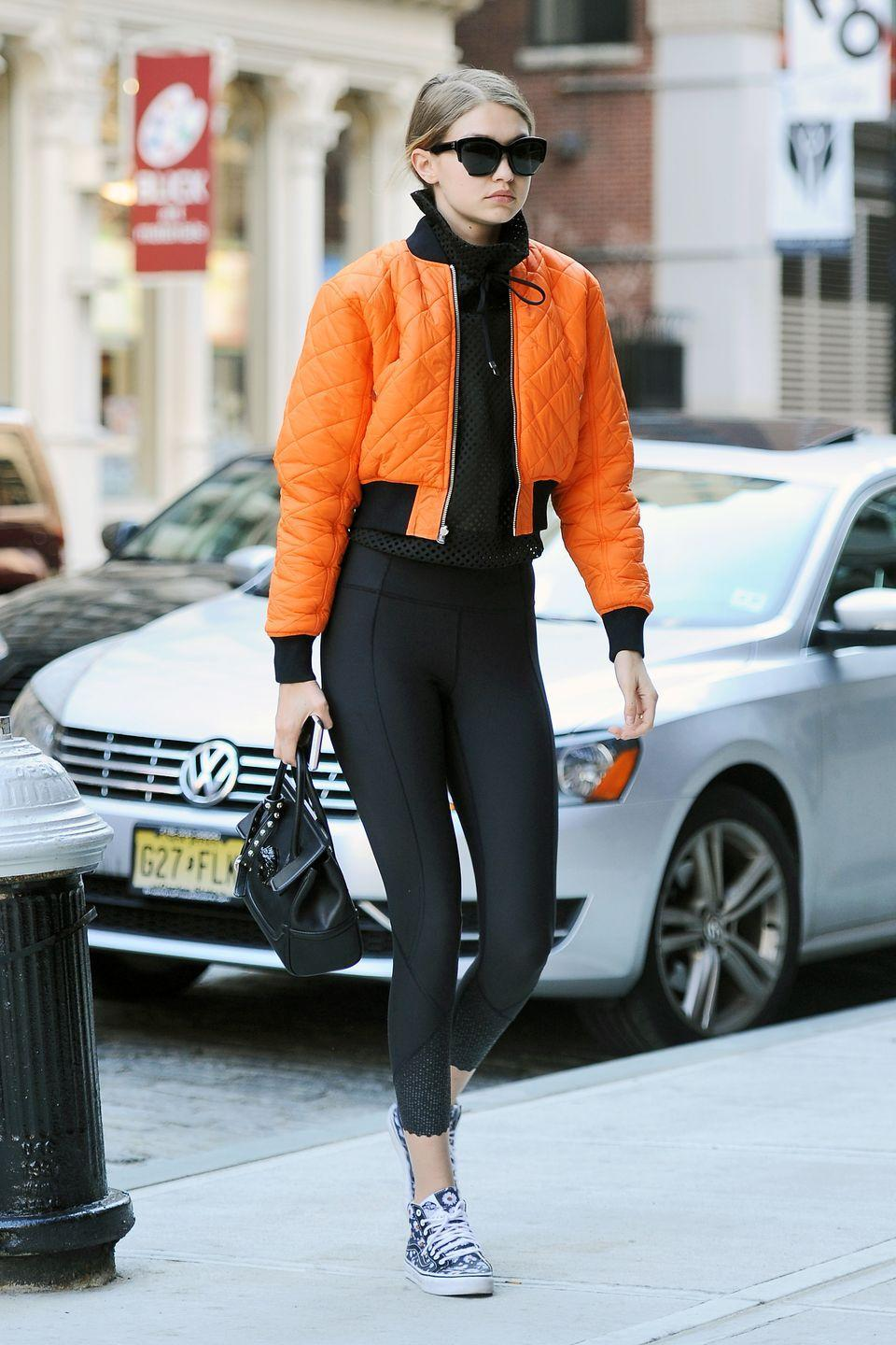 <p>Out in NYC wearing an orange bomber jacket with black leggings and printed sneakers. </p>