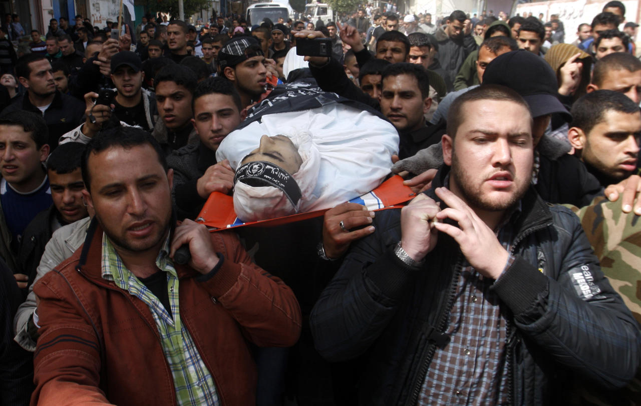 Palestinian carry the body of Ahmed Salim, a member of the armed wing of the Popular Resistance Committees (PRC) who was killed in an Israeli air strike during his funeral in Gaza City , Sunday, March 11, 2012. The worst round of violence in more than a year between Israel and Gaza Strip Palestinians deepened Sunday with deadly Israeli airstrikes and a barrage of rockets fired into the Jewish state. (AP photo/Hatem Moussa)