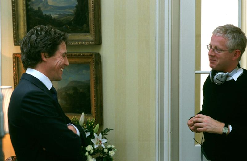 Hugh Grant (left) and Richard Curtis on the Love Actually set in 2002. (Photo: Moviestore/Shutterstock)