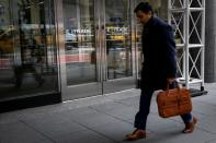 A man passes by E*Trade Financial offices, after it was announced that Morgan Stanley is buying the discount brokerage, in New York