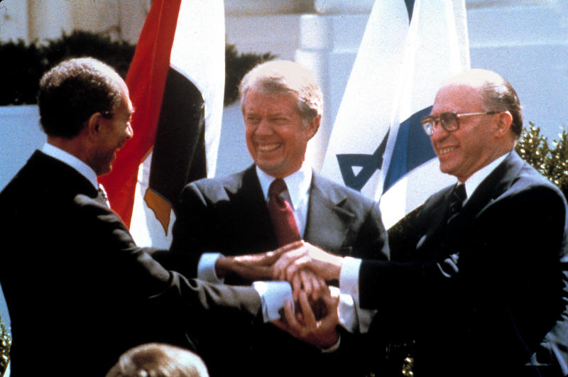 FILE - In this March 26, 1979 file photo, Egyptian President Anwar Sadat, left, U.S. President Jimmy Carter, center, and Israeli Prime Minister Menachem Begin clasp hands on the North lawn of the White House as they completed signing of the peace treaty between Egypt and Israel in Washington. The Central Intelligence Agency has declassified 1,400 pages of intelligence surrounding the Camp David Accords, the historic peace treaty negotiated in 1978 by then-President Jimmy Carter with the leaders of Israel and Egypt, Wednesday, Nov. 13, 2013. (AP Photo/Bob Daugherty, File)