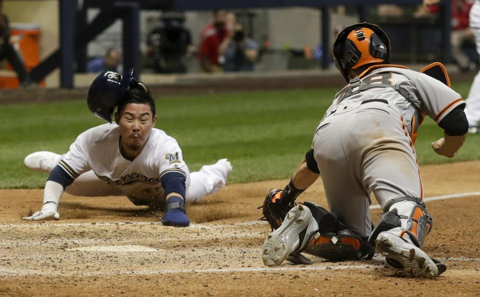 Milwaukee Brewers' Keston Hiura slides safely past San Francisco Giants catcher Buster Posey during the eighth inning of a baseball game Saturday, July 13, 2019, in Milwaukee. Hiura scored from third on a sacrifice fly by Orlando Arcia. (AP Photo/Morry Gash)