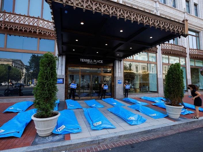 """blue body bags laying on the ground outside facebook's dc office under an awning. the bags bear text that reads """"disinfo kills"""""""