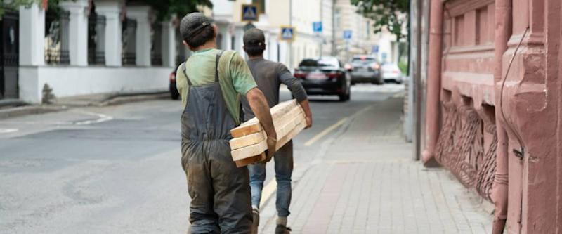 day laborers moving plywood