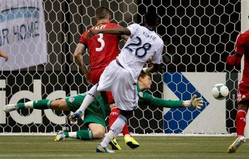 Vancouver Whitecaps' Gershon Koffie (28), of Ghana, scores the only goal of an MLS soccer game against Toronto FC goalkeeper Joe Bendik, back, as Toronto's Danny Califf (3) looks on during the second half in Vancouver, British, Columbia, Saturday, March 2, 2013. (AP Photo/The Canadian Press, Darryl Dyck)