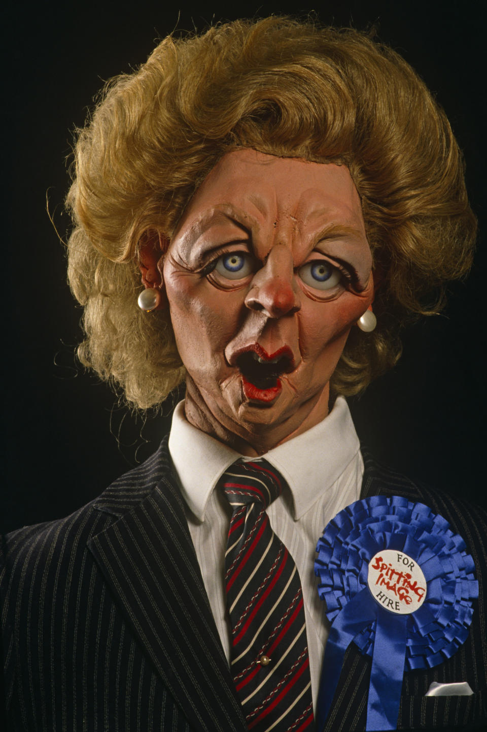 A satirical Margaret Thatcher Spitting Image puppet by Fluck and Law wears a blue Conservative rosette and For Hire sticker. (Photo by In Pictures Ltd./Corbis via Getty Images)