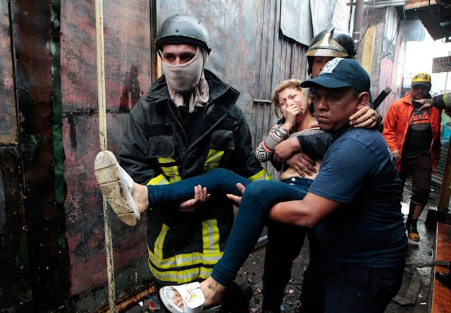 <p>Firefighters help evacuate a woman affected by smoke from a fire at the Oriental Market in Managua, Nicaragua, May 14, 2017. (Photo: Oswaldo Rivas/Reuters) </p>