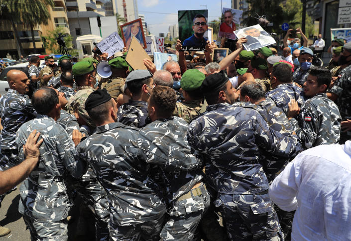 The private security forces of of parliament speaker Nabih Berri, push back the families of the victims of last year's massive blast at Beirut's seaport, as they protest and try to reach his tightly-secured residents, in Beirut, Lebanon, Friday, July 9, 2021. The protest came after last week's decision by the judge to pursue senior politicians and former and current security chiefs in the case, and requested permission for their prosecution. (AP Photo/Hussein Malla)