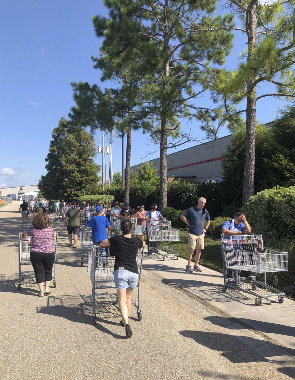 In a photo provided by John Snow, people line up to enter a Costco store Sunday, Aug. 23, 2020, in Baton Rouge, La., as Hurricane Marco was moving toward Louisiana. (John Snow via AP)