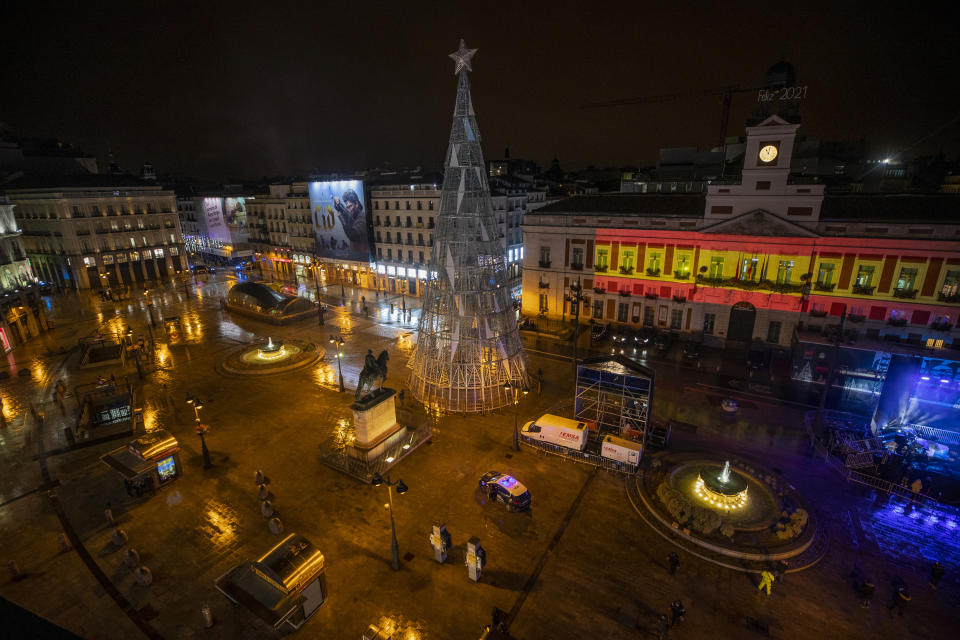 A general view in an empty Madrid's Puerta del Sol before the New Year's celebrations in Madrid, Spain, Thursday, Dec. 31, 2020. Across Spain regional authorities are limiting gatherings to a handful of people while some are slightly relaxing the nightly curfew to allow families to gather before getting home for an early night. (AP Photo/Manu Fernandez)