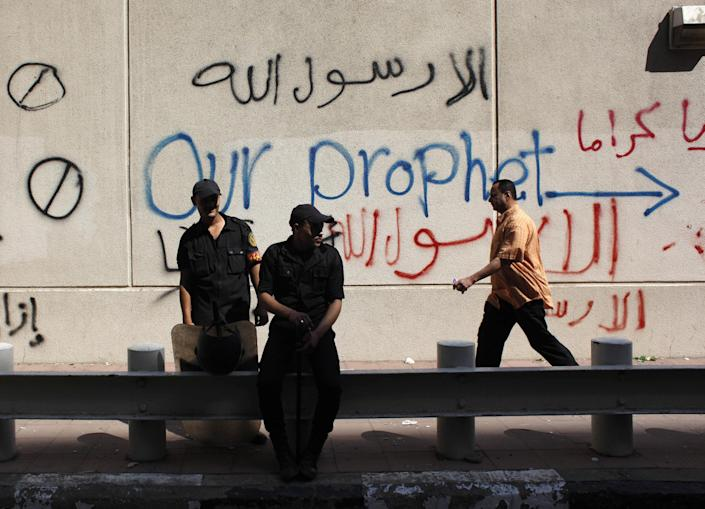 """Egyptian soldiers stand guard in front of the U.S. embassy in Cairo, Egypt, Wednesday, Sept. 12, 2012, as part of widespread anger across the Muslim world about a film ridiculing Islam's Prophet Muhammad. The search for those behind the provocative, anti-Muslim film that triggered mobs in Egypt and Libya led Wednesday to a California Coptic Christian convicted of financial crimes who acknowledged his role in managing and providing logistics for the production. Nakoula Basseley Nakoula, 55, told The Associated Press in an interview outside Los Angeles that he was manager for the company that produced """"Innocence of Muslims,"""" which mocked Muslims and the prophet Mohammed and was implicated in inflaming mobs that attacked U.S. missions in Egypt and Libya. (AP Photo/Nasser Nasser)"""