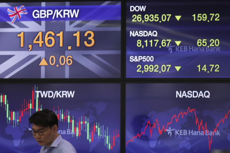 A currency trader stands near screens showing the foreign exchange rates, left, at the foreign exchange dealing room in Seoul, South Korea, Monday, Sept. 23, 2019. Stocks got a downbeat start to the week as investors kept a wary eye on tensions with Iran and on signals from China and the U.S. on prospects for a resolution of their tariffs war. (AP Photo/Lee Jin-man)