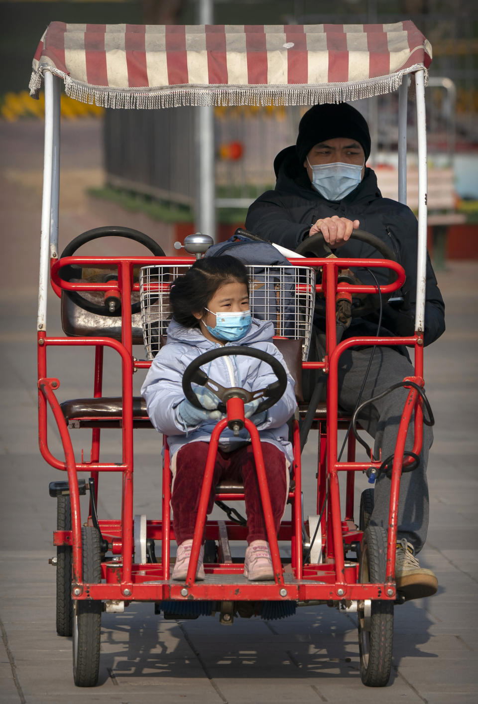 A man and girl wearing face masks to protect against the spread of the coronavirus ride a pedal car at a public park in Beijing, Saturday, Jan. 2, 2021. Wary of another wave of infections, China is urging tens of millions of migrant workers to stay put during next month's Lunar New Year holiday, usually the world's largest annual human migration. (AP Photo/Mark Schiefelbein)