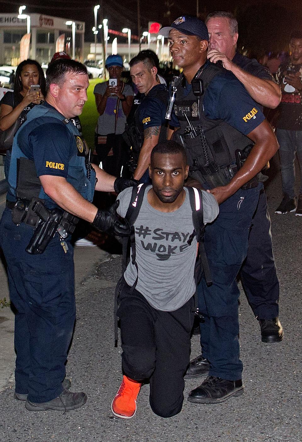 Police officers arrest activist DeRay McKesson during a protest along Airline Highway, a major road that passes in front of the Baton Rouge Police Department headquarters Saturday, July 9, 2016, in Baton Rouge, La. Protesters angry over the fatal shooting of Alton Sterling by two white Baton Rouge police officers rallied Saturday at the convenience store where he was shot, in front of the city's police department and at the state Capitol for another day of demonstrations. (AP Photo/Max Becherer)