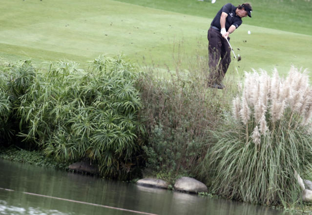 Phil Mickelson of the United States hits a ball on the 9th hole during the first round of the Shanghai HSBC Champions golf tournament at the Sheshan International Golf Club in Shanghai, China, Thursday, Oct. 31, 2013. (AP Photo/Eugene Hoshiko)