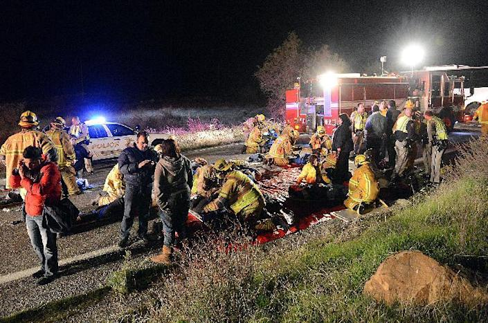 Authorities work the scene where at least eight people were killed and nearly two dozen were injured when a bus carrying a group from Tijuana, Mexico crashed with two other vehicles on its way back from Big Bear Lake on Highway 38 north of Yucaipa, Calif., Sunday, Feb. 3, 2013. Both sides of the highway remained closed two and a half hours after the crash and it was unclear when it would reopen. (AP Photo/The Sun, Rick Sforza) MANDATORY CREDIT