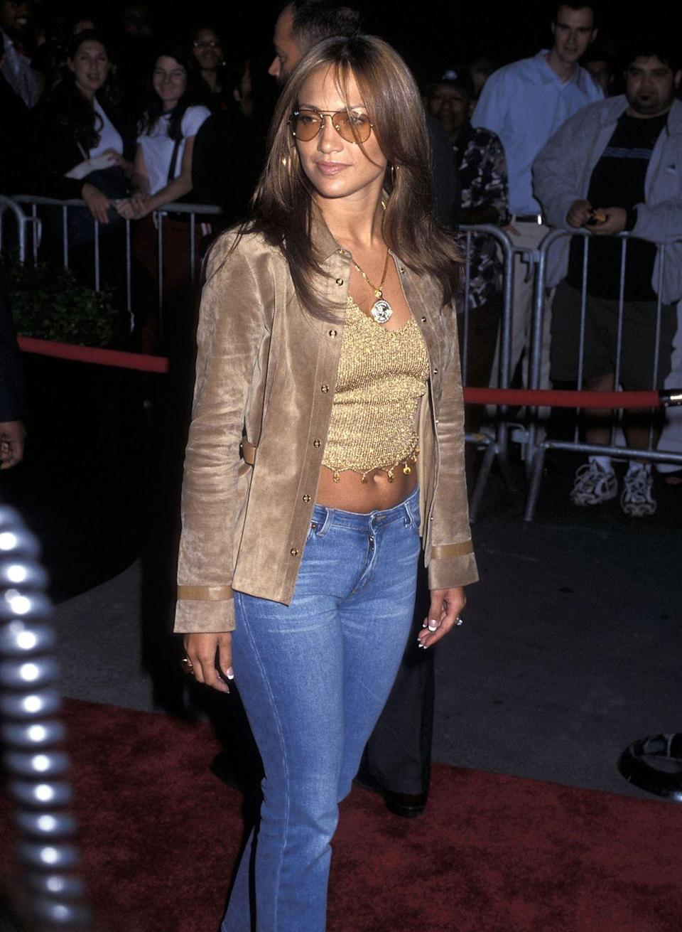 <p>Jennifer Lopez red carpet look at the <em>Bamboozled </em>premiere ticked off several early '00s fashion boxes. Low-rise jeans, a sparkly crop top, suede jacket, and light sunglasses make this a fall fave.</p>