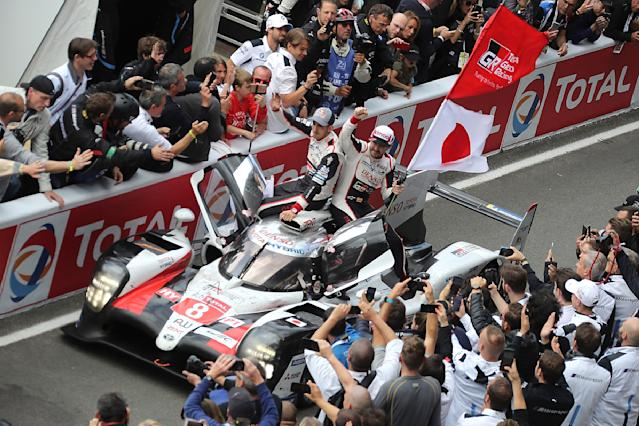 The Toyota TS050 Hybrid No8 of the Toyota Gazoo Racing Team driven by Sebastien Buemi of Switzerland, Kazuki Nakajima of Japan and Fernando Alonso of Spain celebrates with their fans as they win the 87th 24-hour Le Mans endurance race, in Le Mans, western France, Sunday, June 16, 2019. (AP Photo/David Vincent)
