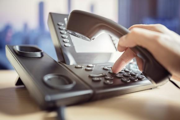 A person uses a land line telephone.