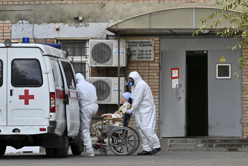 Medical workers wearing protective gear transport a patient suspected of having coronavirus from an ambulance to a hospital in Rostov-on-Don, Russia, Thursday, Oct. 22, 2020. Russia is facing a sharp rise in infections, but the Kremlin has ruled out a new lockdown. (AP Photo)